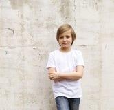 Netter blonder Junge in den Jeans und in einem weißen Hemd Stockfoto
