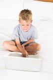 Netter blonder Junge, der auf Bett unter Verwendung des Laptops sitzt Stockfotografie