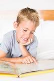 Netter blonder Junge, der auf dem Bett liest ein Märchenbuch liegt Lizenzfreie Stockfotos