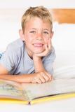 Netter blonder Junge, der auf dem Bett liest ein Märchenbuch liegt Lizenzfreie Stockbilder