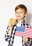 Netter blonder Junge, der Cheeseburger isst Stockbild