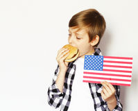 Netter blonder Junge, der Cheeseburger isst Lizenzfreie Stockbilder
