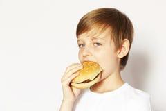Netter blonder Junge, der Cheeseburger isst Stockfoto