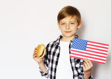 Netter blonder Junge, der Cheeseburger isst Stockbilder