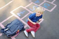 Netter blonder Junge, der das Hopsespiel nach der Schule mit den Taschen nahe legen spielt Stockbilder
