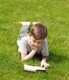 Netter blonder Junge, der ein Buch in einem Park liest Stockbilder