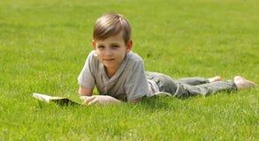 Netter blonder Junge, der ein Buch in einem Park liest Stockfoto