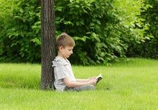 Netter blonder Junge, der ein Buch in einem Park liest Stockfotografie