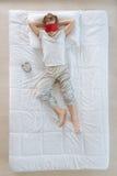 Netter blonder Junge, der eine Schlafenmaske trägt Stockbilder