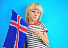 Netter blonder Junge, der Flagge von Island hält lizenzfreies stockbild
