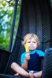 Netter blonder Junge, der gelbe Wassereiscreme, draußen isst Lizenzfreie Stockfotos