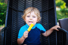 Netter blonder Junge, der gelbe Wassereiscreme, draußen isst Lizenzfreie Stockfotografie