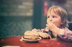 Netter netter blonder Junge, der im Café mit Stück des Kuchens sitzt Lizenzfreie Stockfotografie