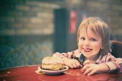 Netter netter blonder Junge, der im Café mit Stück des Kuchens sitzt Stockfotos