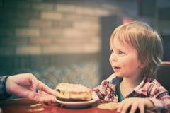 Netter netter blonder Junge, der im Café mit Stück des Kuchens sitzt Stockfoto