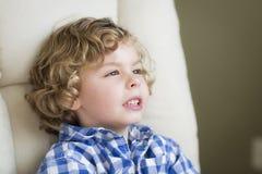 Netter blonder Junge, der im Stuhl träumt und sitzt Lizenzfreies Stockfoto