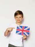 Netter blonder Junge, der mit britischer Flagge aufwirft Stockfoto