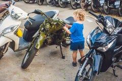 Netter blonder Junge, der neues Motorrad der Weinlesemotorrad-Esswaren betrachtet Stockfoto