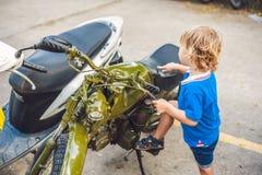 Netter blonder Junge, der neues Motorrad der Weinlesemotorrad-Esswaren betrachtet Lizenzfreies Stockbild