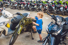 Netter blonder Junge, der neues Motorrad der Weinlesemotorrad-Esswaren betrachtet Lizenzfreie Stockfotos