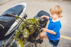 Netter blonder Junge, der neues Motorrad der Weinlesemotorrad-Esswaren betrachtet Stockfotografie