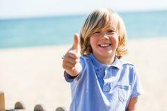 Netter blonder Junge, der oben Daumen am Strand tut. Stockfotos