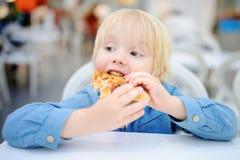 Netter blonder Junge, der Scheibe der Pizza am Schnellrestaurant isst Lizenzfreies Stockbild