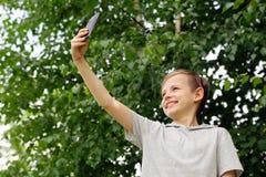 Netter blonder Junge, der selfie in einem Park tut Stockfoto