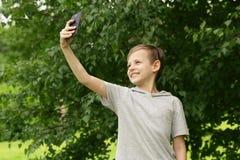 Netter blonder Junge, der selfie in einem Park tut Stockfotografie