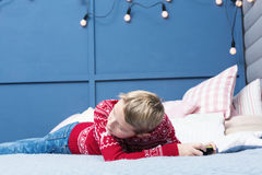 Netter blonder Junge, der Spiel am Handy spielt Lizenzfreie Stockbilder