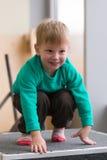 Netter blonder Junge in der Turnhalle auf einem Sockel Stockfotos