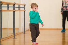 Netter blonder Junge in der Turnhalle auf einem Sockel Stockbild