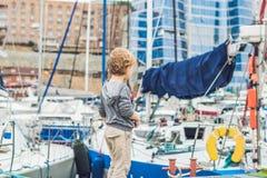 Netter blonder Junge, der Yachten und Segelboote betrachtet Lizenzfreies Stockbild
