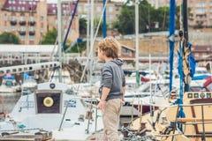 Netter blonder Junge, der Yachten und Segelboote betrachtet Stockbilder
