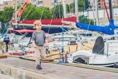 Netter blonder Junge, der Yachten und Segelboote betrachtet Lizenzfreie Stockbilder