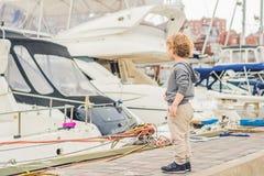 Netter blonder Junge, der Yachten und Segelboote betrachtet Stockfoto