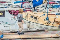 Netter blonder Junge, der Yachten und Segelboote betrachtet Lizenzfreie Stockfotos