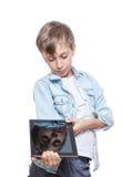 Netter blonder Junge in einem blauen Hemd, das einen braunen Tabletten-PC hält Stockfotografie