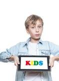 Netter blonder Junge in einem blauen Hemd, das einen Tabletten-PC hält Lizenzfreies Stockfoto