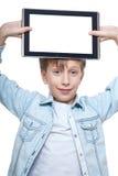 Netter blonder Junge in einem blauen Hemd, das einen Tabletten-PC mit weißem Schirm hält Lizenzfreies Stockfoto