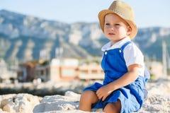 Netter blonder Junge im Hut und im blauen Gesamten Lizenzfreie Stockfotografie