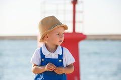 Netter blonder Junge im Hut und im blauen Gesamten Lizenzfreies Stockfoto