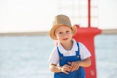 Netter blonder Junge im Hut und im blauen Gesamten Stockbild