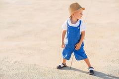 Netter blonder Junge im Hut und im blauen Gesamten Stockfotografie