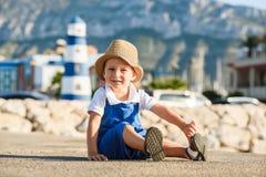 Netter blonder Junge im Hut und im blauen Gesamten Lizenzfreies Stockbild