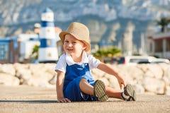Netter blonder Junge im Hut und im blauen Gesamten Lizenzfreie Stockfotos