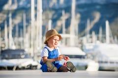 Netter blonder Junge im Hut und im blauen Gesamten Stockfotos
