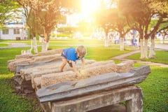 Netter blonder Junge klettert oben die Steinblöcke auf dem Spielplatz Kindheit, Konzept Stockfoto