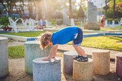 Netter blonder Junge klettert oben die Steinblöcke auf dem Spielplatz Kindheit, Konzept Stockfotografie