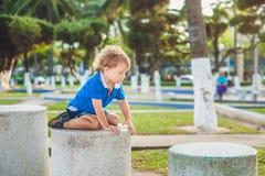 Netter blonder Junge klettert oben die Steinblöcke auf dem Spielplatz Kindheit, Konzept Lizenzfreies Stockfoto